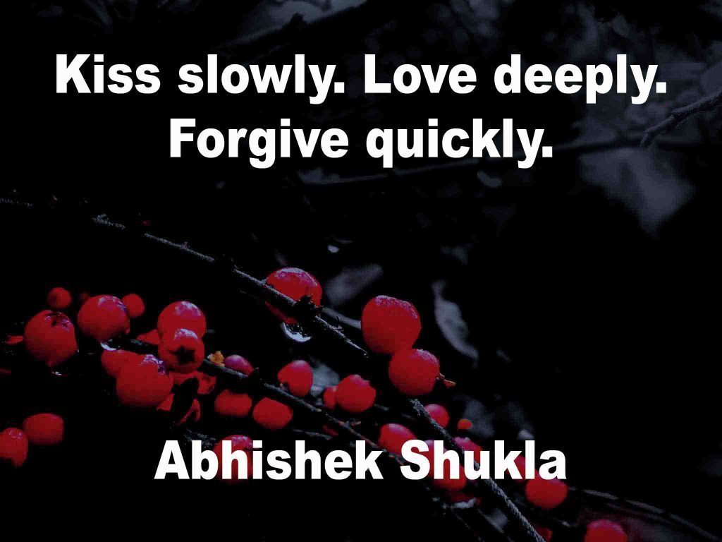 The image shows a spray of red berries on a black background on which a quotation by Abhishek Shukla is written. It speaks of kissing slowly, loving deeply and forgiving quickly.
