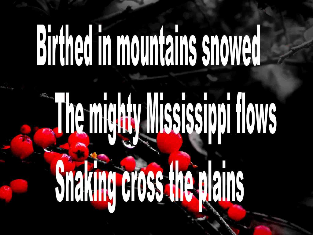 The image shows a spray of red berries on a black background on which a haiku poem titled Birthed in Mountains Snowed by the poet Goff James. The poem  speaks of the mighty Mississippi River being birthed in snow covered mountains and snaking its way cross the plains..