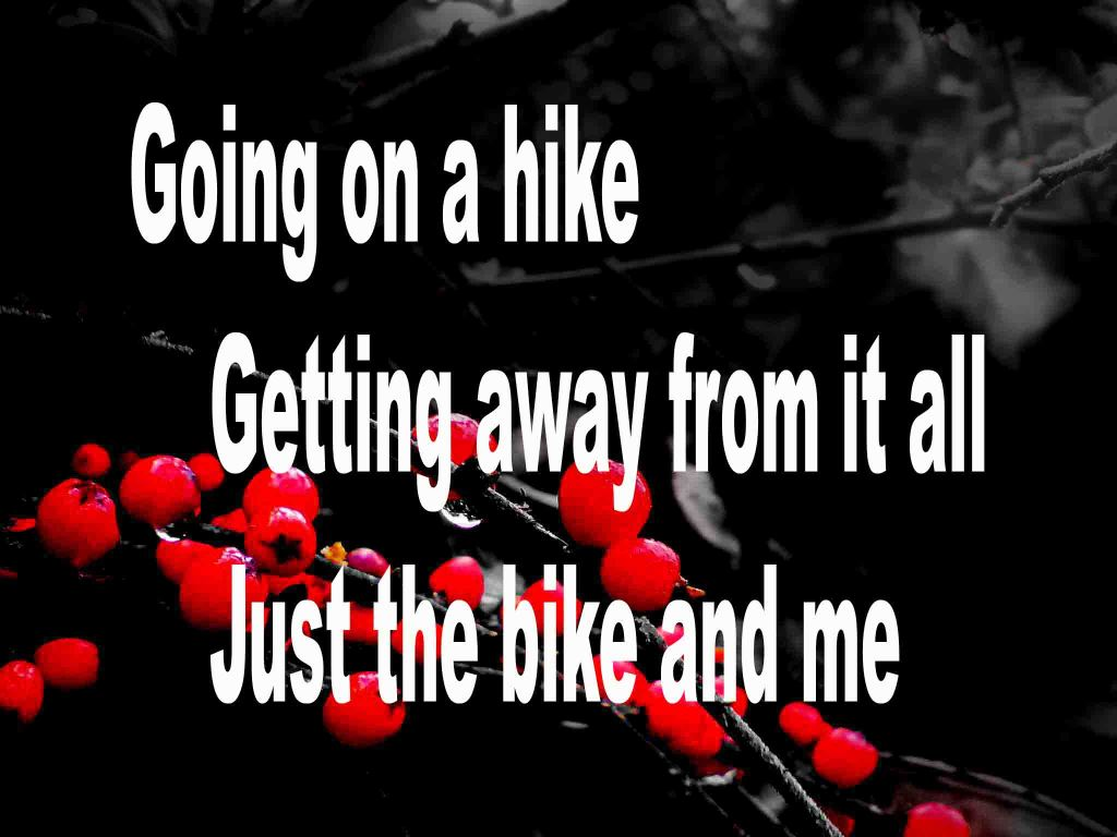 The image shows a spray of red berries on a black background on which a haiku titled Going on a Hike is written. The poem speaks of getting away from it all by taking a trip, alone, on a bicycle.