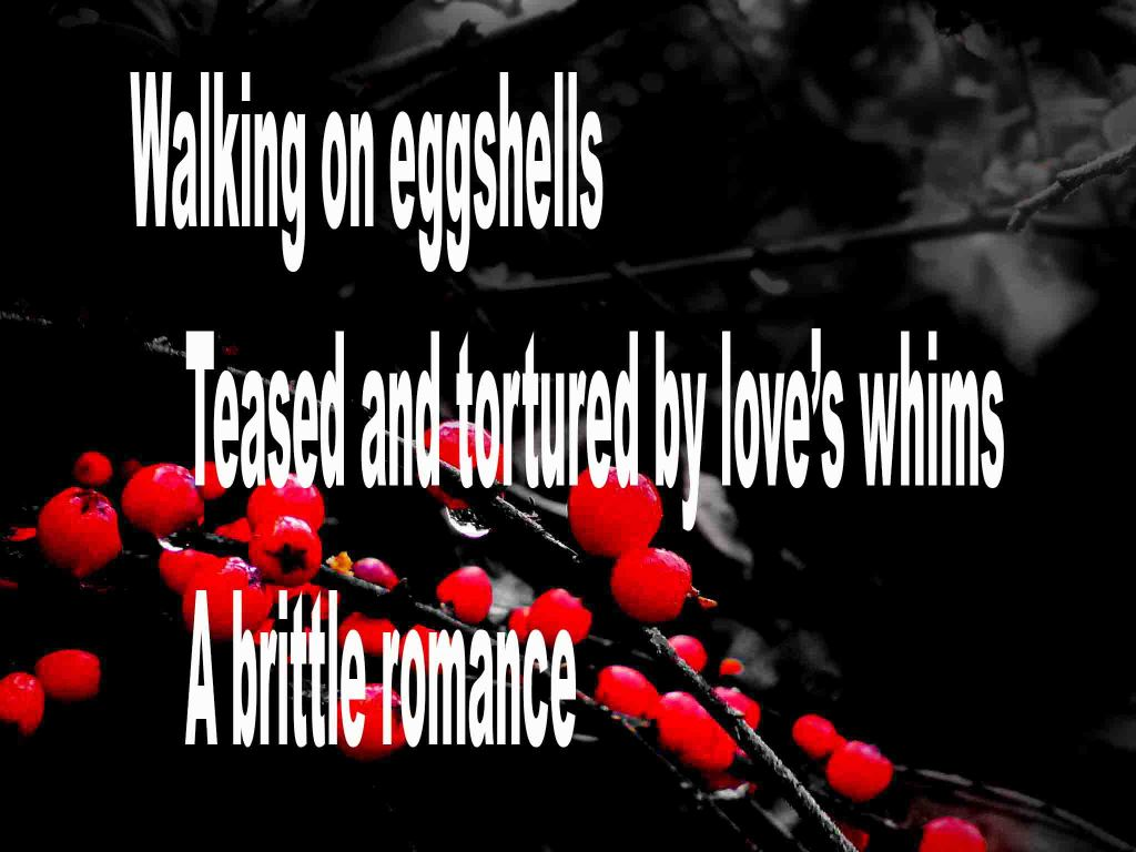 The image shows a spray of red berries on a black background on which a haiku titled Walking on Eggshells is written. The poem speaks of being teased and tortured by love's whims.