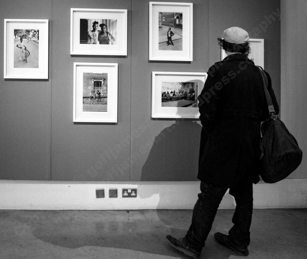 The image depicts a back lit black and white photograph of the back view of a male gallery visitor dressed in a cap, overcoat long trousers, shoes and carrying a large holdall over his right shoulder. The figure is set to the right of the frame and is viewing a series of black and white photographs hanging on the gallery wall. Th viewer's shadows fall on the wall and floor.