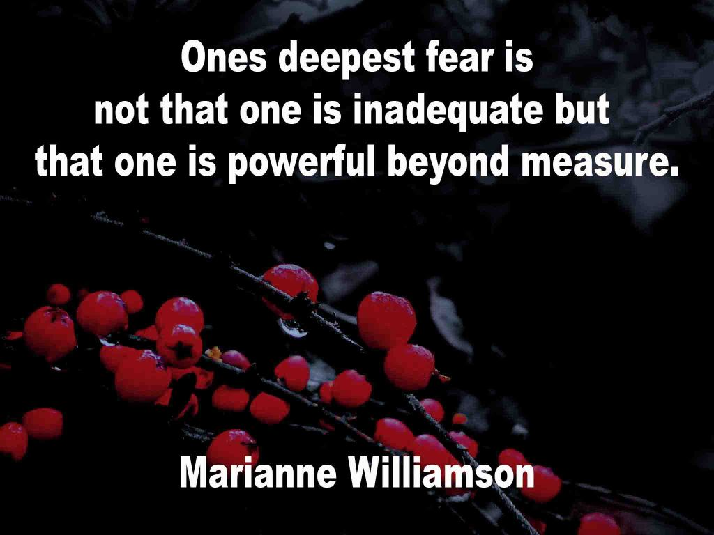The image shows a spray of red berries on a black background on which a quotation by Marianne Williamson is written. It speaks of ones deepest fear being not that one is inadequate but that one is powerful beyond measure.