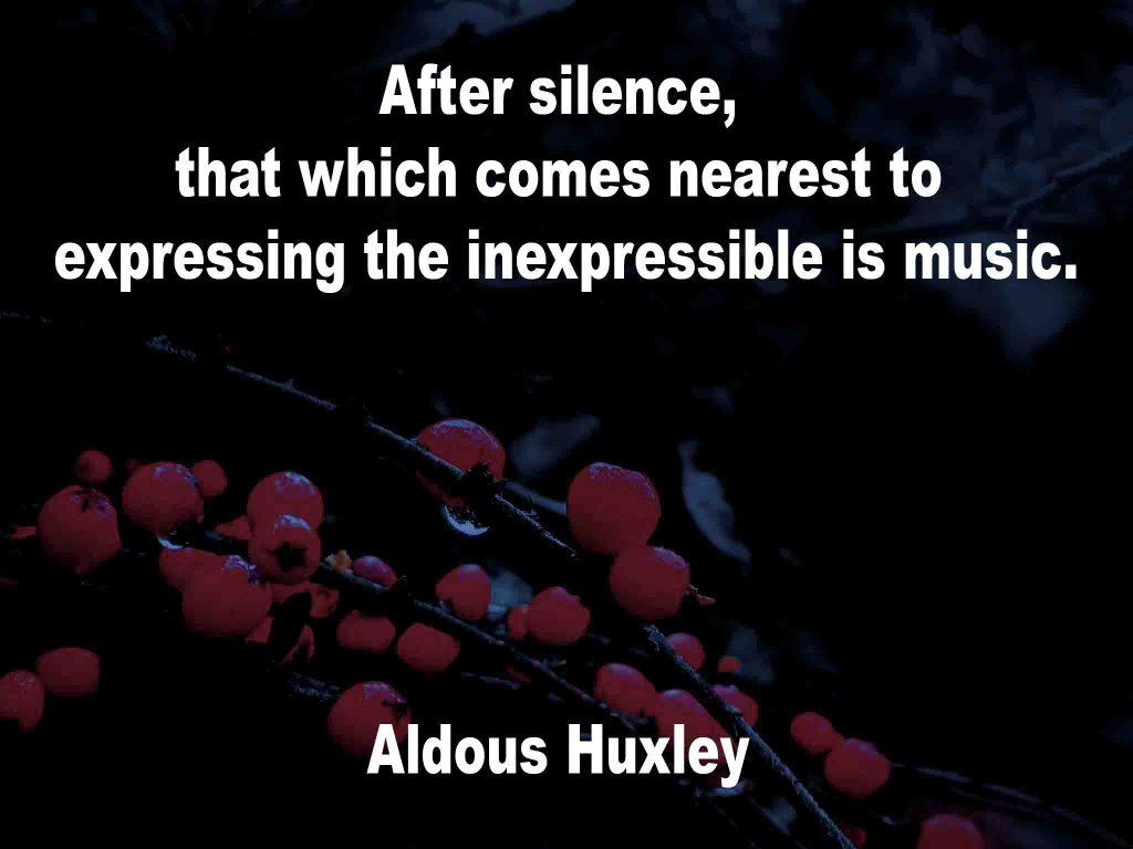 The image shows a spray of red berries on a black background on which a music quotation by Aldous Huxley is written. It speaks of that which comes nearest to expressing the inexpressible, after silence, is music.
