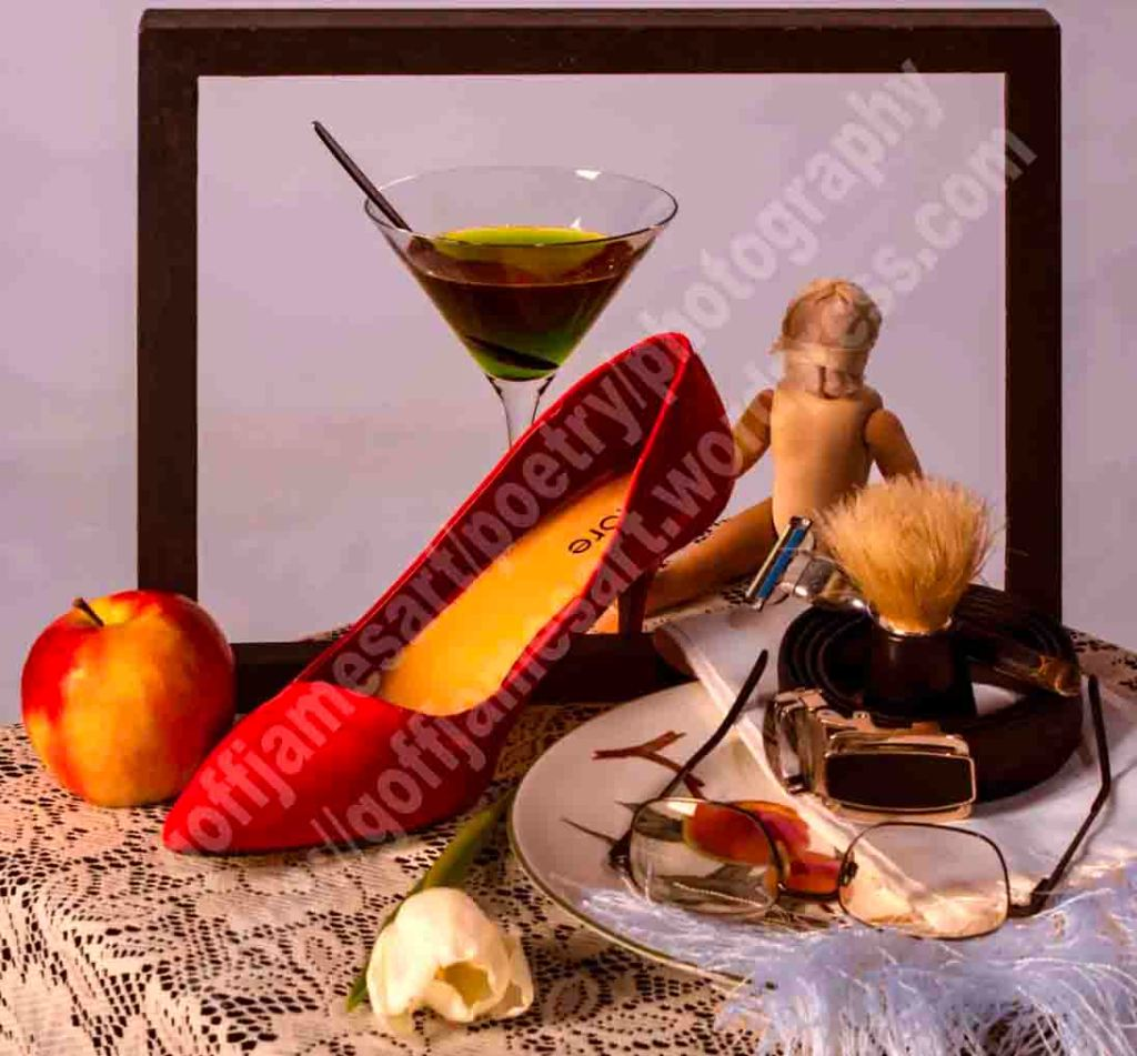 The image depicts a photograph titled Still Life with Apple by the photographer. The work is a colour photo of an assemblage of many different objects, martini glass, apple, doll, red stiletto shoe, patterned dinner plate, white tulip, silk white scarf, mans leather belt and shaving brush, framed within a black picture frame, set on a white lace tablecloth against a pale plain lavender background. .
