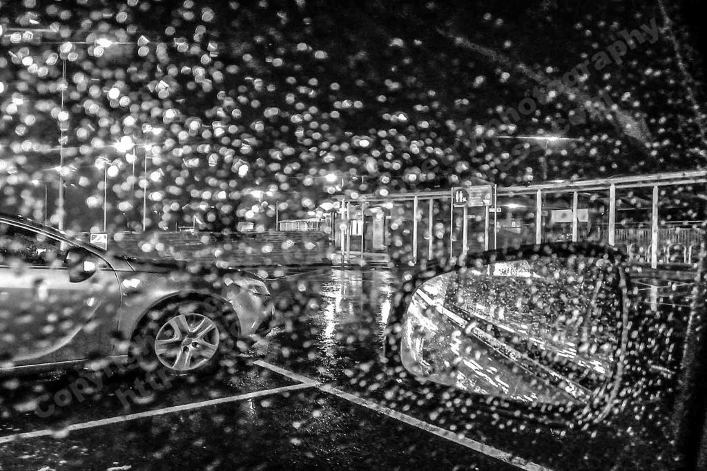 The image depicts a photograph titled Without Words 444 by the photographer. The work is a black and white night-time photo of a supermarket car park in the rain.